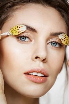 Sluit omhoog van mooi jong meisje met perfecte schone huid en alstroemeria bloemblaadjes bekijkend camera over witte achtergrond. gezichtsbehandeling. schoonheid en spa.