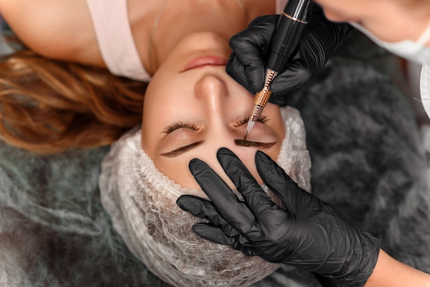 Sluit omhoog van mooi vrouwengezicht met dikke wenkbrauwen in schoonheidssalon. permanente make-up voor wenkbrauwen.