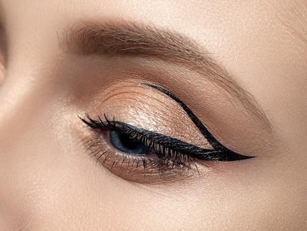 Sluit omhoog van mooi vrouwenoog met mooie moderne eyeliner-vleugel