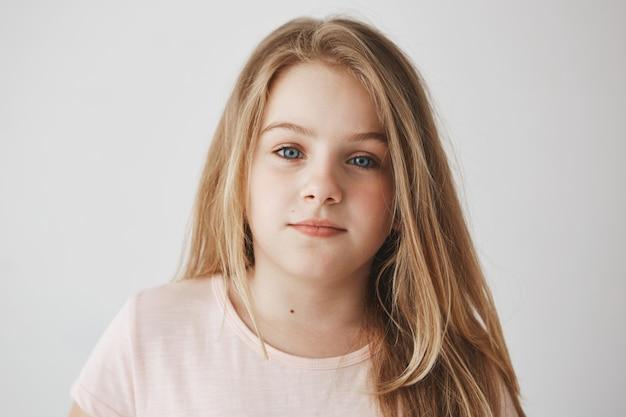 Sluit omhoog van mooi weinig blondemeisje met licht lang haar en heldere blauwe ogen. kind met ontspannen expressie