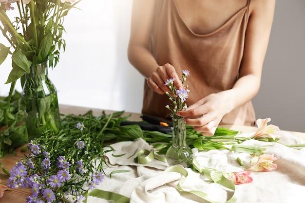 Sluit omhoog van mooie afrikaanse vrouwenbloemist die boeket in bloemenwinkel maken over witte muur.