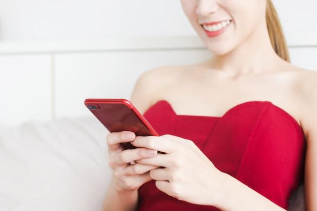Sluit omhoog van mooie aziatische vrouw op de rode rode telefoon en de glimlach van het kledingsspel