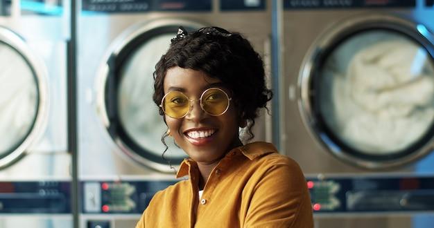Sluit omhoog van mooie jonge afrikaanse amerikaanse vrouw die in gele zonnebril vrolijk aan camera in wasserijdienst glimlachen. portret van vrij gelukkig meisje dat met wasmachines lacht