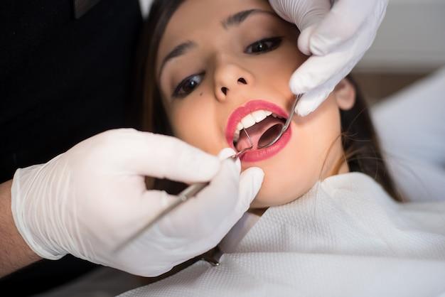 Sluit omhoog van mooie jonge vrouw die tandcontrole omhoog in tandbureau hebben. tandarts die de tanden van een patiënt met tandhulpmiddelen onderzoeken - spiegel en sonde
