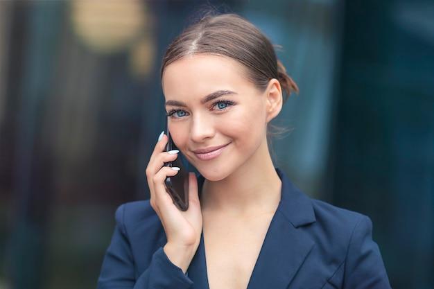Sluit omhoog van mooie positieve gelukkige bedrijfsvrouw die op mobiele telefoon spreekt