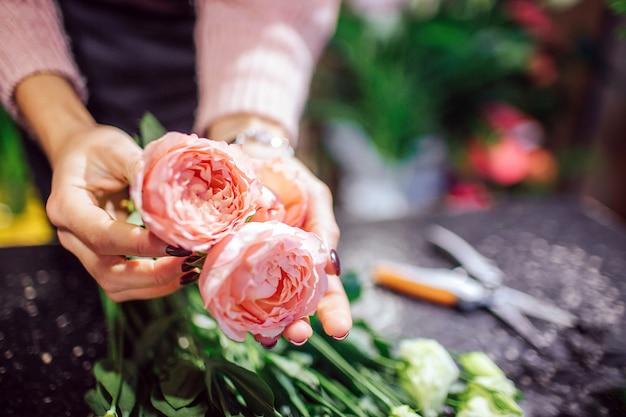 Sluit omhoog van mooie sinaasappel met de roze in hand greep van de rozenvrouw. schaar en groene planten staan achter bloemen.