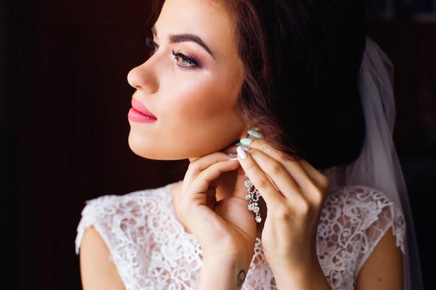 Sluit omhoog van mooie vrouw die met make-up juwelenoorringen draagt