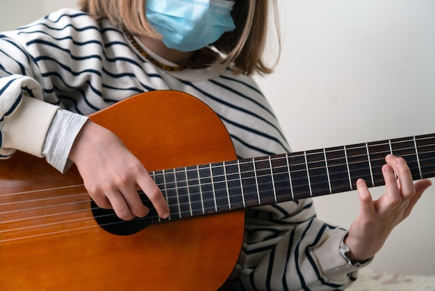Sluit omhoog van musicus die medisch gezichtsmasker draagt en gitaar speelt