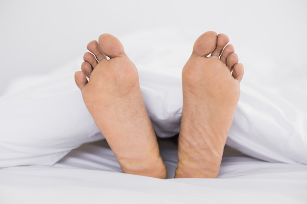 Sluit omhoog van naakte voeten in bed