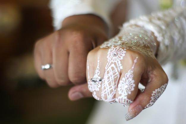 Sluit omhoog van nieuwe gehuwde parenhanden die hun trouwringen tonen