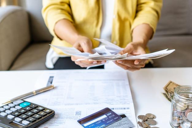 Sluit omhoog van onderneemster die rekeningen controleren en maandelijkse kosten berekenen bij haar bureau. home opslaan concept. financiële en termijnbetaling concept.