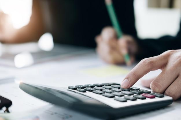 Sluit omhoog van onderneemster of accountantshand die pen houden die aan calculator werken om bedrijfsgegevens, boekhoudingsdocument en laptop computer op kantoor, bedrijfsconcept te berekenen