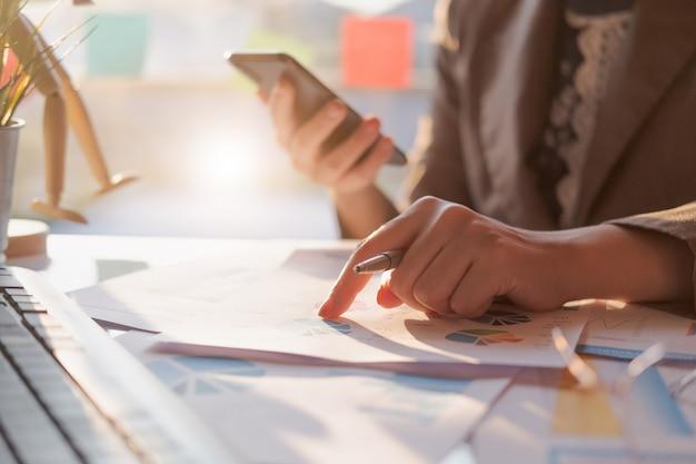 Sluit omhoog van onderneemster of het potlood die van de accountantshand aan het slimme rapport van telefoongegevens, boekhoudingsdocument en laptop computer op kantoor, bedrijfsconcept werken