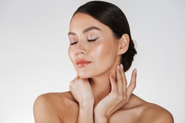 Sluit omhoog van ontspannen donkerbruine vrouw met het zachte huid stellen bij camera met gesloten ogen, geïsoleerd over wit