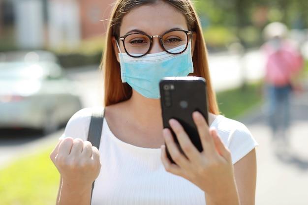 Sluit omhoog van opgewekte jonge bedrijfsvrouw die met chirurgisch masker goed nieuws bij het mobiele telefoon vieren met omhoog vuist in stadsstraat ontvangen