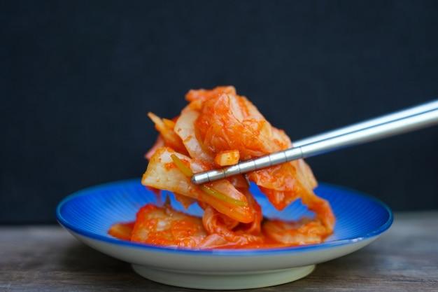 Sluit omhoog van organisch koreaans kimchivoedsel met eetstokjes