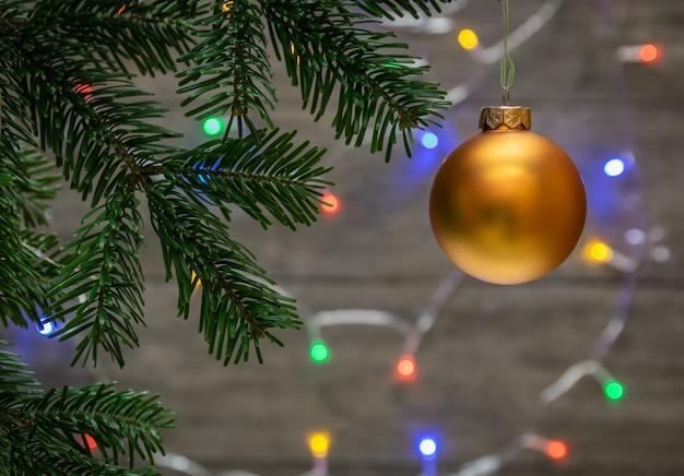 Sluit omhoog van ornamenten op een takjekerstboom en achtergrond met kleurrijke lichten