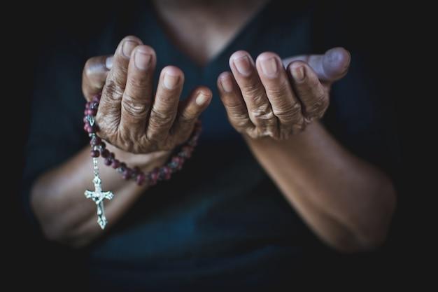 Sluit omhoog van oude handen die op zwarte achtergrond bidden