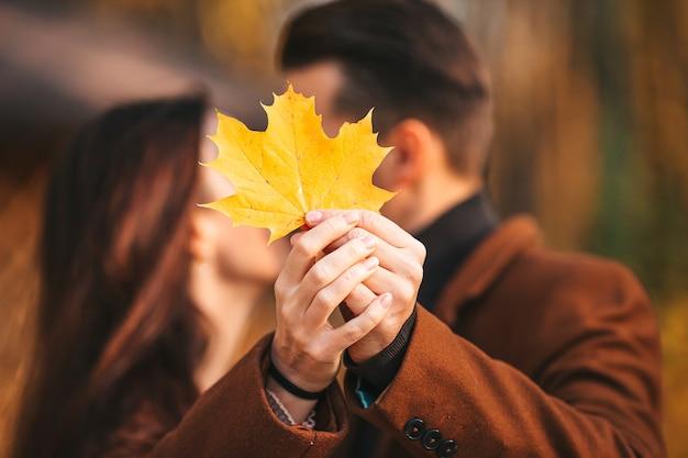 Sluit omhoog van paar met het gele kussen van het esdoornblad in de herfstpark