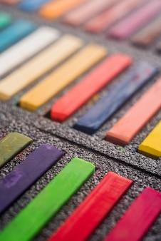Sluit omhoog van pastelkleurverven in zwarte doos