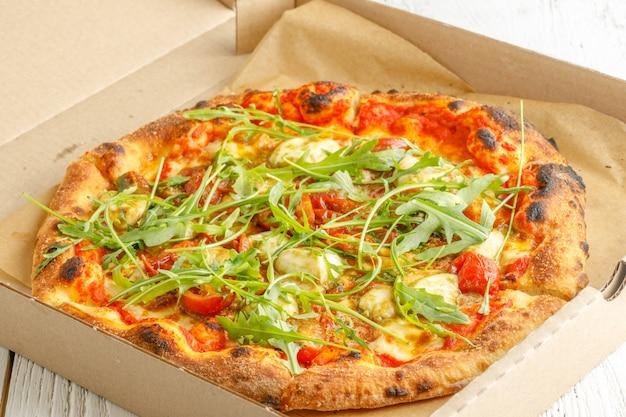 Sluit omhoog van pizza's met verscheidenheid van greens en kaas in karton
