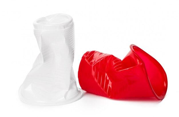 Sluit omhoog van plastic koppen voor dranken op wit