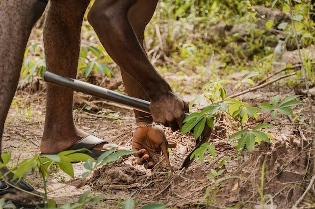 Sluit omhoog van plattelandsarbeider die de grond controleert