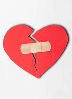 Sluit omhoog van pleister en document gebroken hart op witte achtergrond.