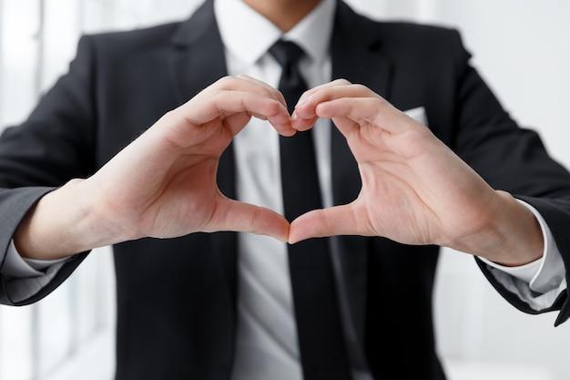 Sluit omhoog van portret van zakenman die een hart met zijn handen maakt.