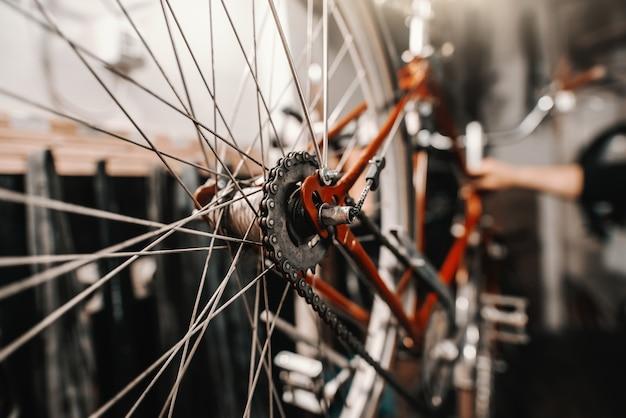 Sluit omhoog van radertje dat op fiets wordt geplaatst. bike workshop interieur.
