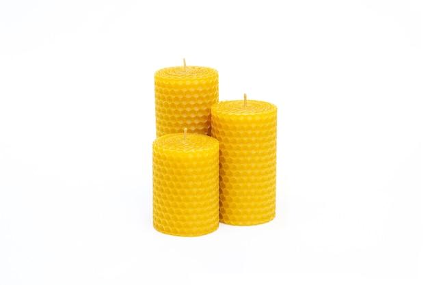 Sluit omhoog van reeks van drie gele decoratieve natuurlijke bijenwaskaarsen met een honingaroma voor binnenland dat op witte achtergrond wordt geïsoleerd
