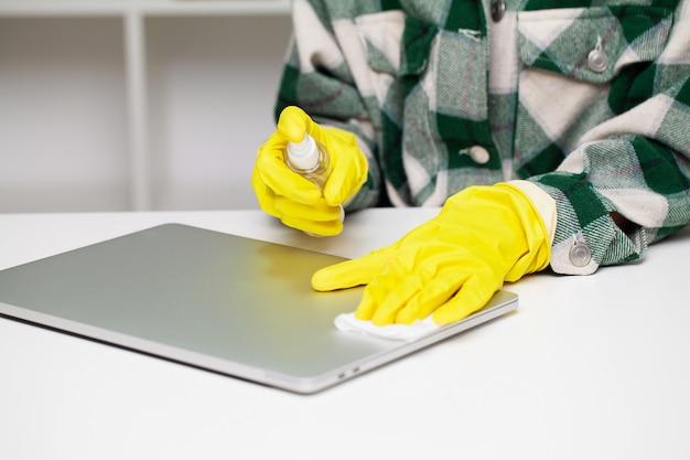 Sluit omhoog van reinigingsmachine in gele handschoenen veegt stof in het bureau af