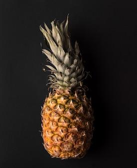 Sluit omhoog van rijpe ananas die over zwarte wordt geïsoleerd