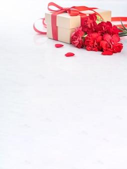 Sluit omhoog van rode anjer met giftdoos voor moederdaggroet