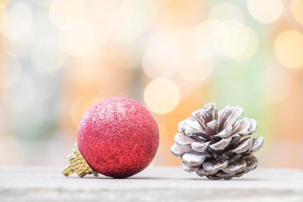 Sluit omhoog van rode bal en pinecone voor kerstmis of nieuwjaardecoratieachtergrond