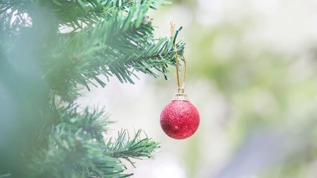 Sluit omhoog van rode bal en pinecone voor kerstmis op vage lichten
