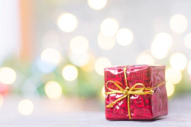 Sluit omhoog van rode giftdoos voor kerstmis op vage lichten