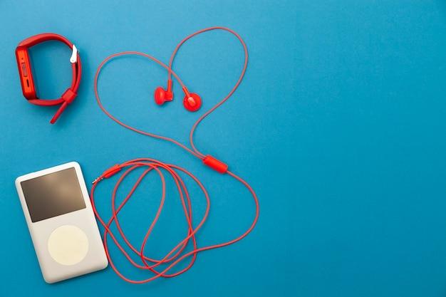 Sluit omhoog van rode oortelefoons met sporthorloge en muziekspeler op blauw document achtergrond.
