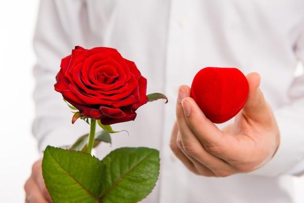 Sluit omhoog van rode roos en trouwringdoos