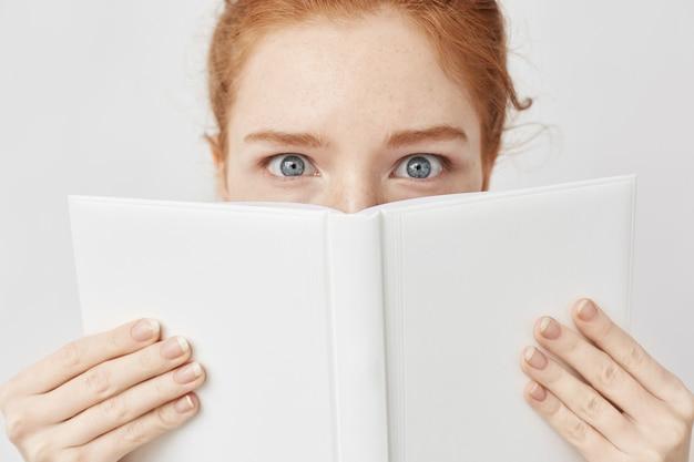 Sluit omhoog van roodharigevrouw met blauwe ogen achter boek.