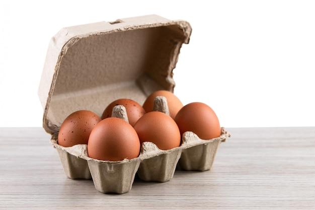 Sluit omhoog van ruwe kippeneieren in eivakje, natuurvoeding van natuurlijk op rustieke houten lijst