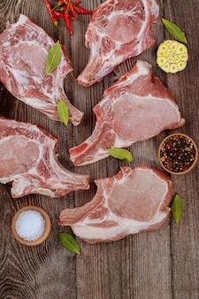 Sluit omhoog van ruwe varkenskotelettenrib met kruiden op grijze achtergrond. bovenaanzicht.