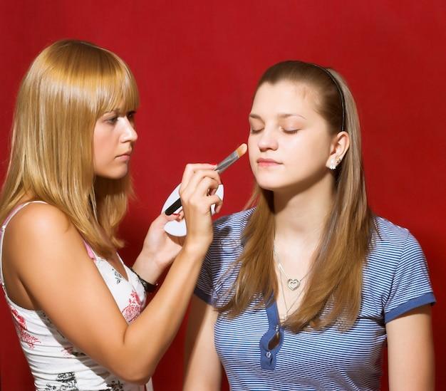 Sluit omhoog van schoonheidsspecialist die make-up voor jonge vrouwen in de schoonheidssalon creëren.