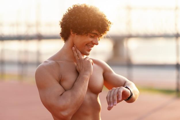 Sluit omhoog van shirtless glimlachende sportieve mens die hartslag controleren na het lopen