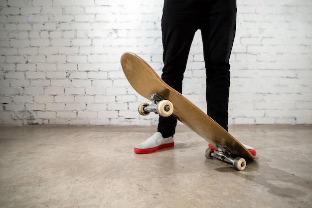 Sluit omhoog van skateboarder die zich naast een witte bakstenen muur bevindt.