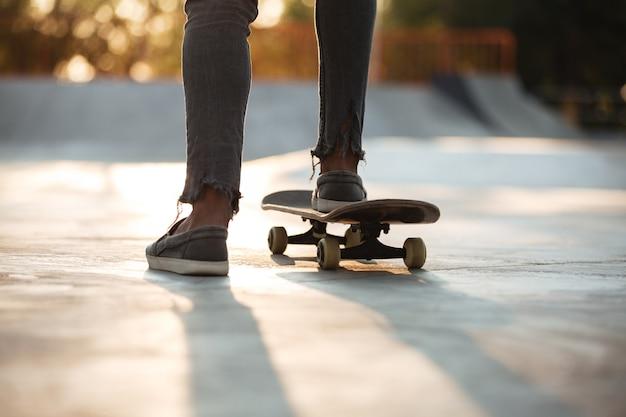Sluit omhoog van skateboardersvoeten het schaatsen