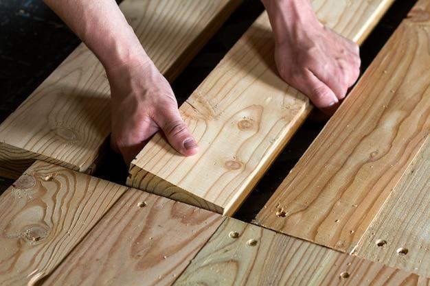 Sluit omhoog van sterke spierhanden van professionele timmerman die natuurlijke houten nieuwe planken op houten kadervloer installeren wederopbouw, verbetering, vernieuwing en timmerwerkconcept.