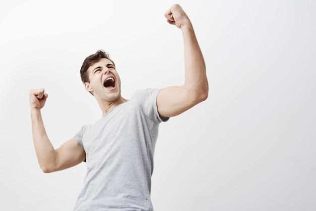 Sluit omhoog van succesvolle jonge kaukasische mannelijke sportman die ja gillen en gebalde vuisten in de lucht opheffen, opgewekt voelend. mensen, succes, triomf, overwinning, winnen en feest.