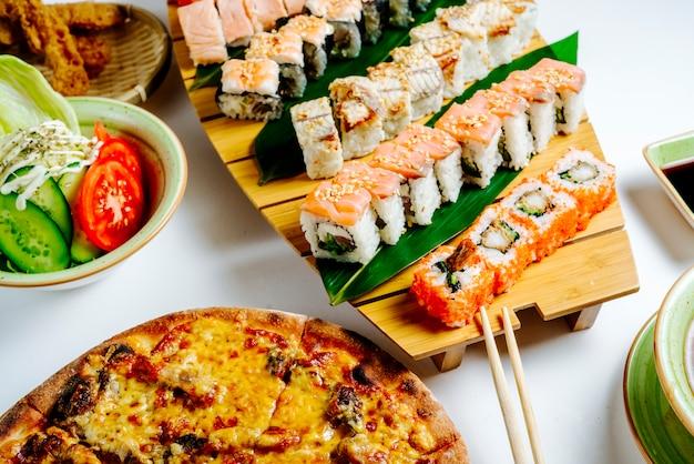 Sluit omhoog van sushi die naast pizza en salade worden geplaatst