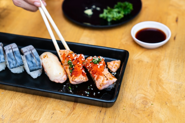 Sluit omhoog van sushi met eetstokjes en soja op houten lijst worden geplaatst die.